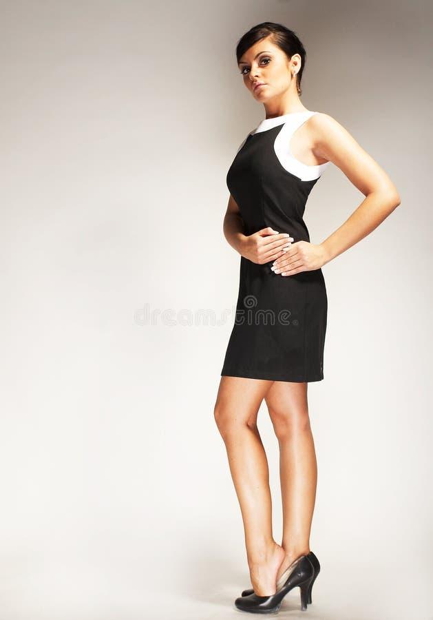 Modèle de mode sur le fond clair dans la robe noire photo libre de droits