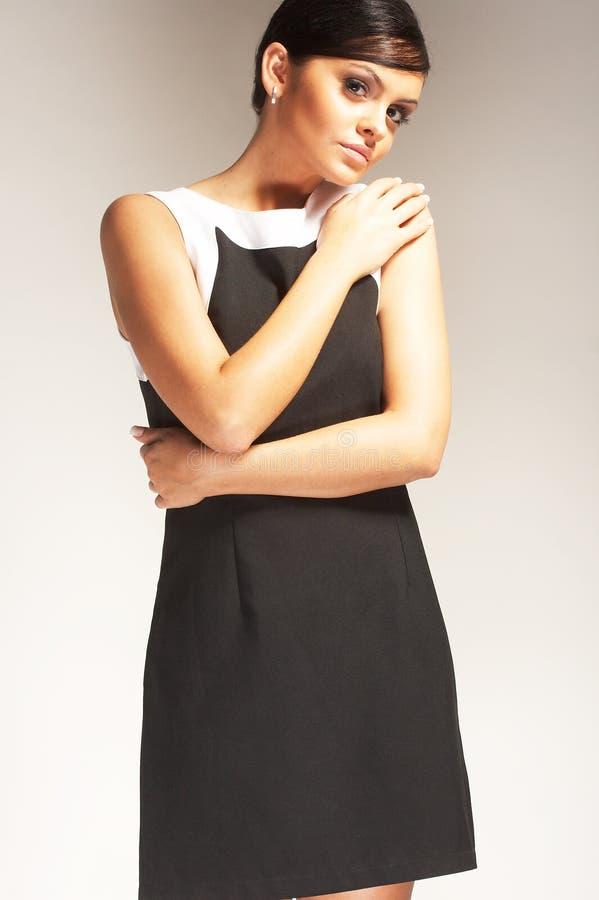 Modèle de mode sur le fond clair dans la robe noire images libres de droits