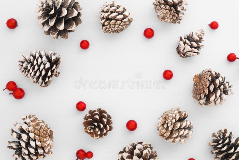 Modèle de Noël fait de cônes de pin et baies rouges sur le fond blanc image libre de droits