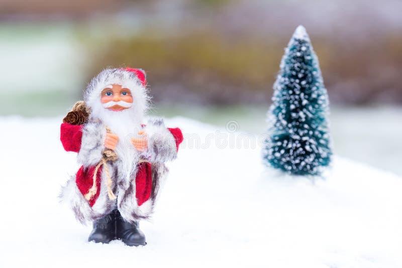 Modèle de Santa Claus se tenant dans la neige blanche dehors images stock