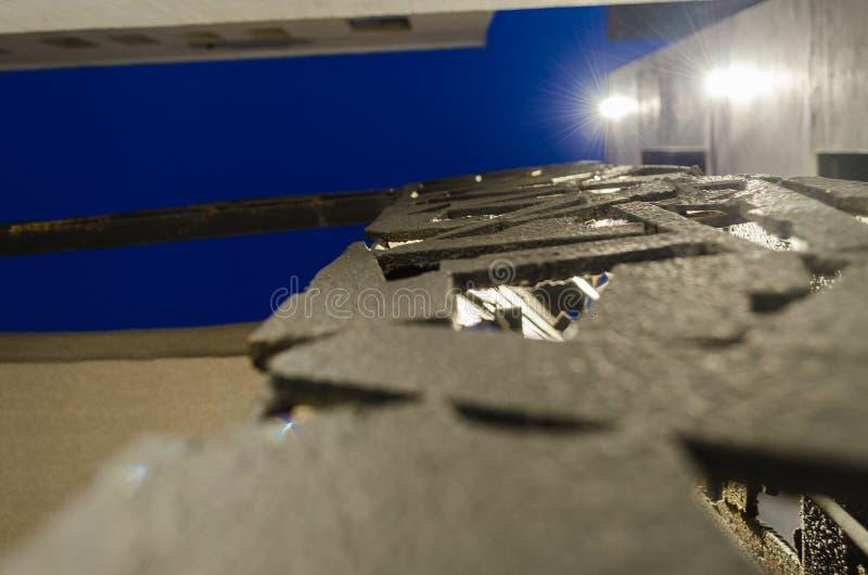 Modèle des constructions métalliques de couleur noire, avec des bâtiments à l'arrière-plan et à un beau ciel bleu photo stock