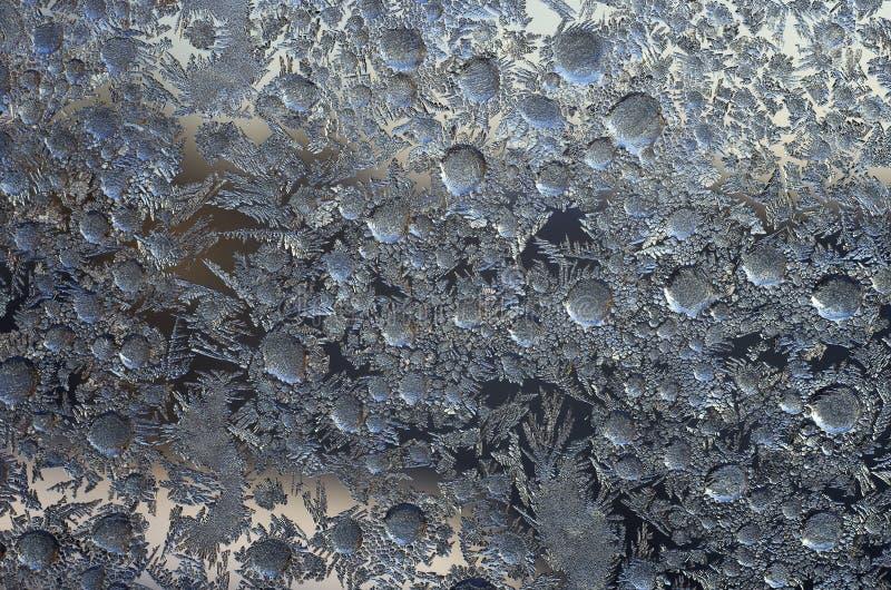 Modèle des cristaux de glace sur le verre, une fin  photo stock