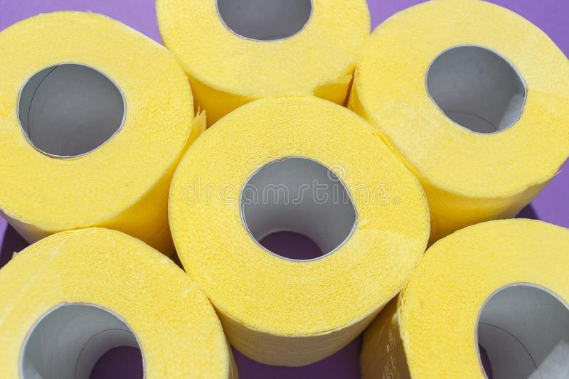 Modèle des petits pains jaunes lumineux de papier hygiénique sur le fond pourpre Composition plate, vue supérieure images libres de droits