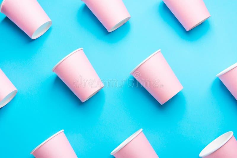 Modèle des tasses de papier roses de boissons disposées diagonalement sur les milieux bleus en bon état Mode d'abrégé sur célébra images stock