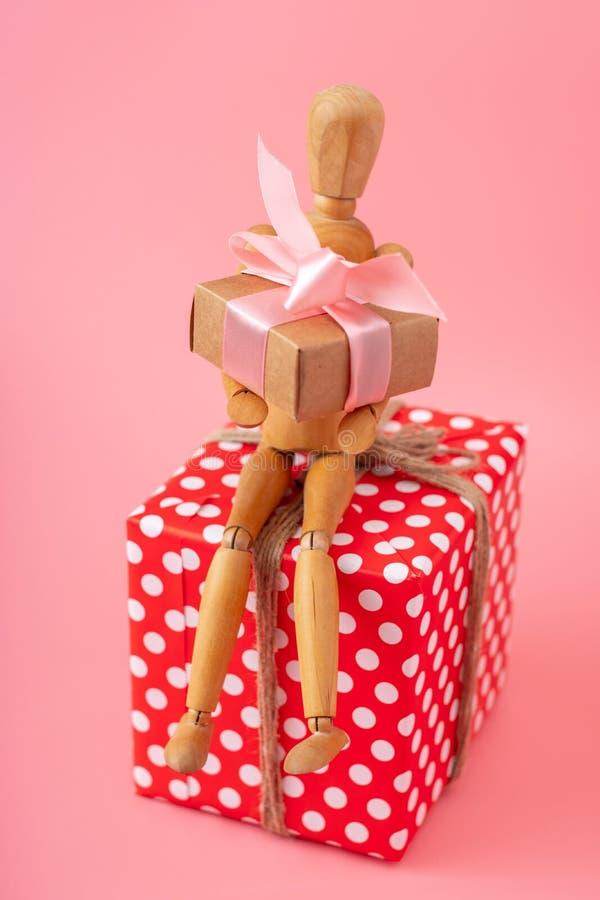 Modèle en bois de jouet tenant des cadeaux se reposant sur une boîte rouge sur le fond rose Carte de vacances pour la Saint-Valen photographie stock