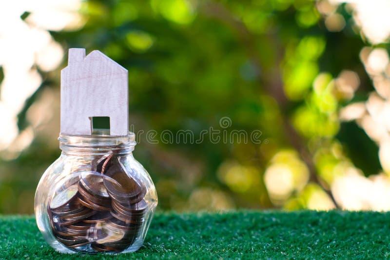 Modèle en bois de maison sur le pot en verre qui plein des pièces de monnaie Prêt hypothécaire à l'habitation et concept d'invest image stock