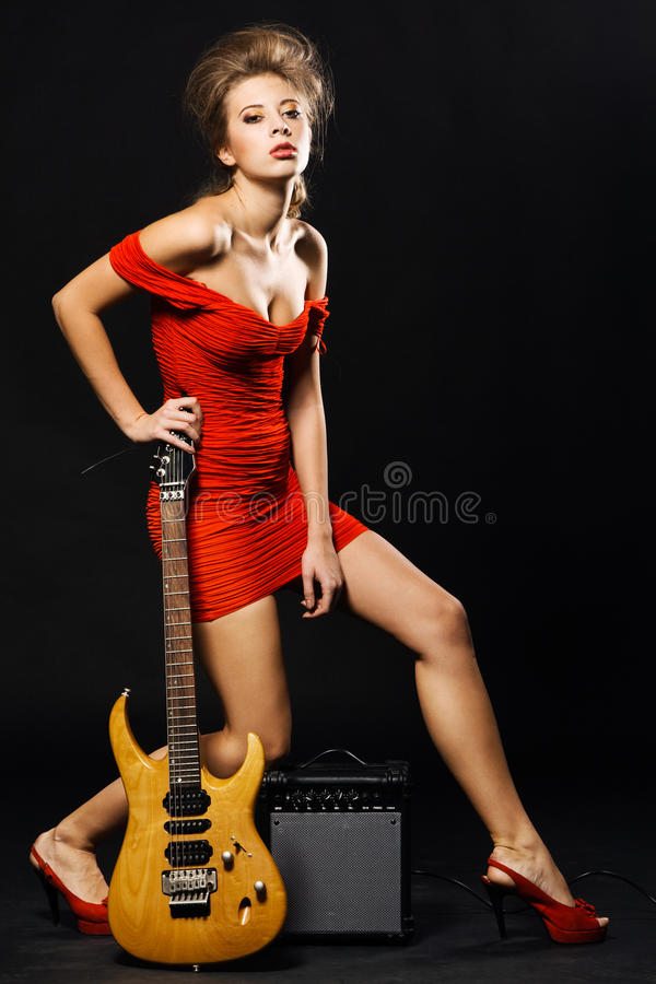 Modèle exagéré avec la guitare et l'amplificateur photographie stock libre de droits