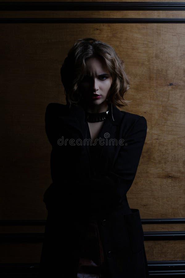 Modèle fâché de brune avec les cheveux bouclés posant avec la lumière de contraste photos libres de droits