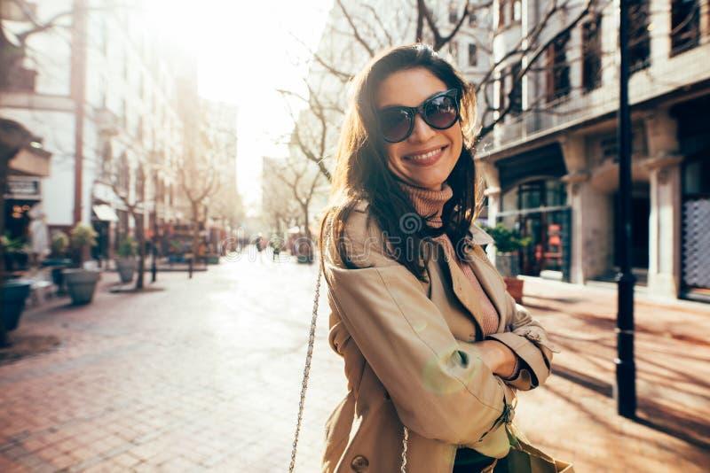 Modèle femelle élégant avec des lunettes de soleil sur la rue de ville photo stock