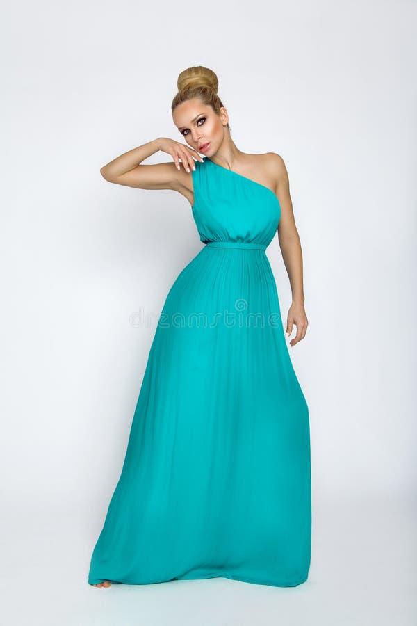 Modèle femelle élégant dans une longue robe en soie de turquoise se tenant sur un fond blanc image libre de droits