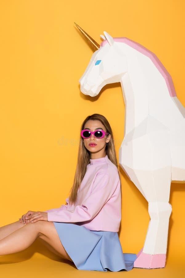 modèle femelle asiatique élégant dans les lunettes de soleil et la licorne décorative sur le jaune photographie stock libre de droits