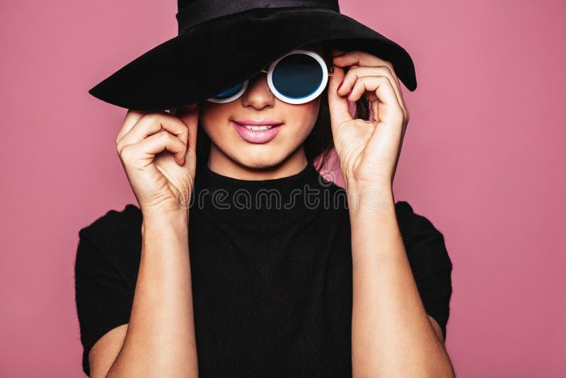 Modèle femelle avec le chapeau et les lunettes de soleil élégantes photographie stock