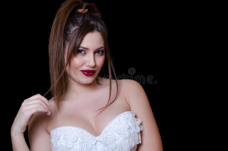Modèle femelle de Babyface portant la robe blanche sans bretelles sur le fond noir photographie stock libre de droits