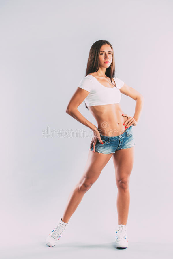 Modèle femelle de forme physique dans les vêtements de sport sur le fond gris photos stock
