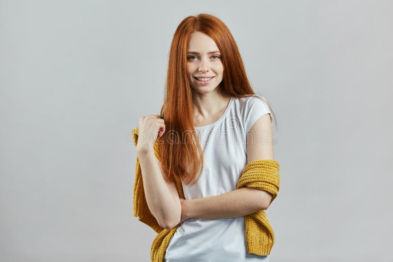 Modèle femelle de gingembre impressionnant dans des vêtements élégants posant à la caméra photo libre de droits