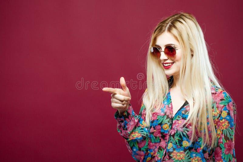 Modèle femelle mignon avec des lunettes de soleil et de longs cheveux utilisant la chemise colorée sur le fond rose La blonde éto images stock