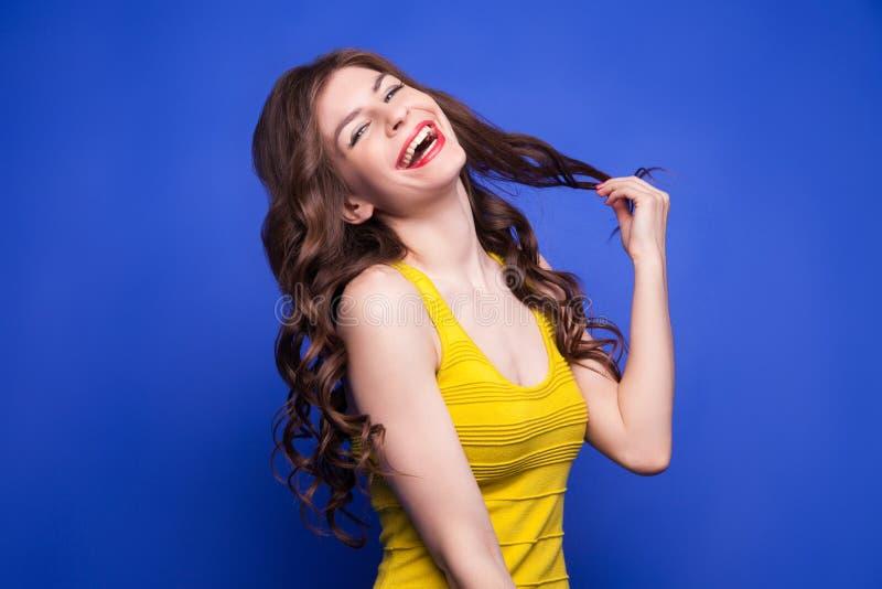 Modèle gai dans la robe jaune tirant ses cheveux photo stock
