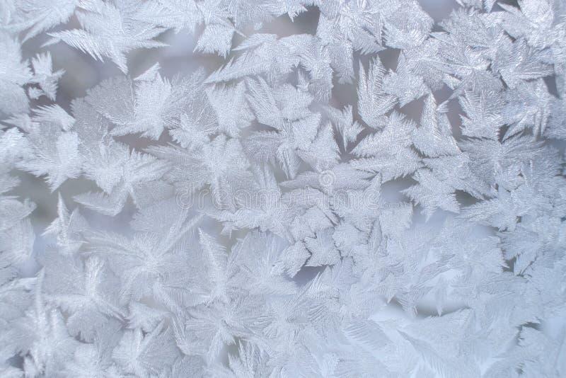 Modèle givré d'hiver sur le carreau de fenêtre avec de grands flocons de neige de fantaisie photos libres de droits