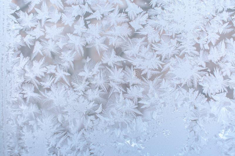 Modèle givré de beaucoup de flocons de neige aigus sur le verre de fenêtre Sel photos libres de droits