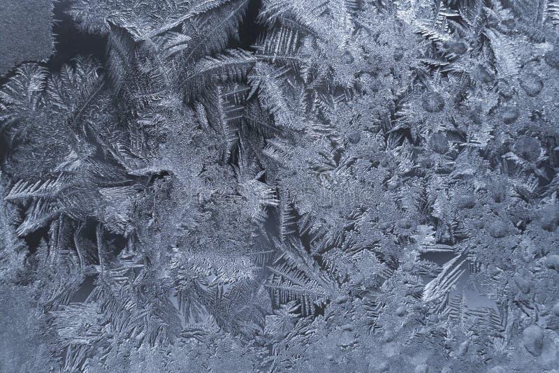 Modèle glacial givré richement décoré naturel sur la fenêtre d'hiver Texture glaciale gelée photos libres de droits