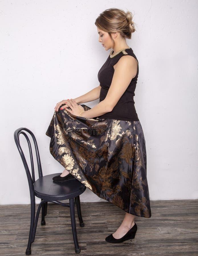 Modèle habillé pour la partie en noir et or images stock