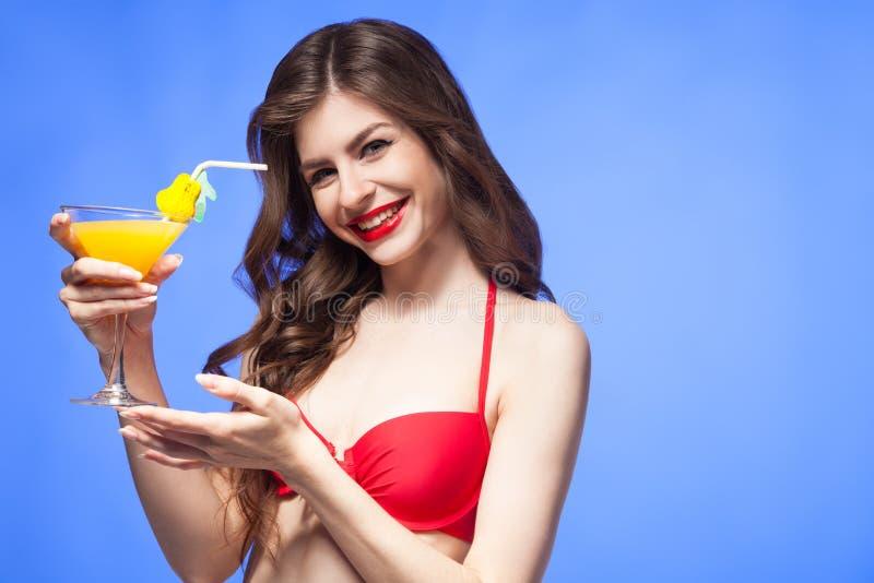 Modèle heureux dans le bikini rouge présentant le cocktail exotique photos stock