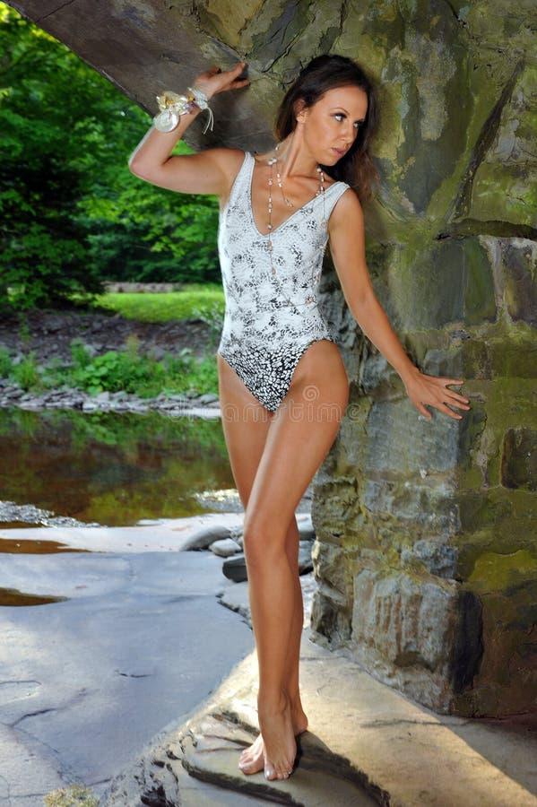 Modèle magnifique de brune dans le maillot de bain de conception posant à l'emplacement de nature photo libre de droits