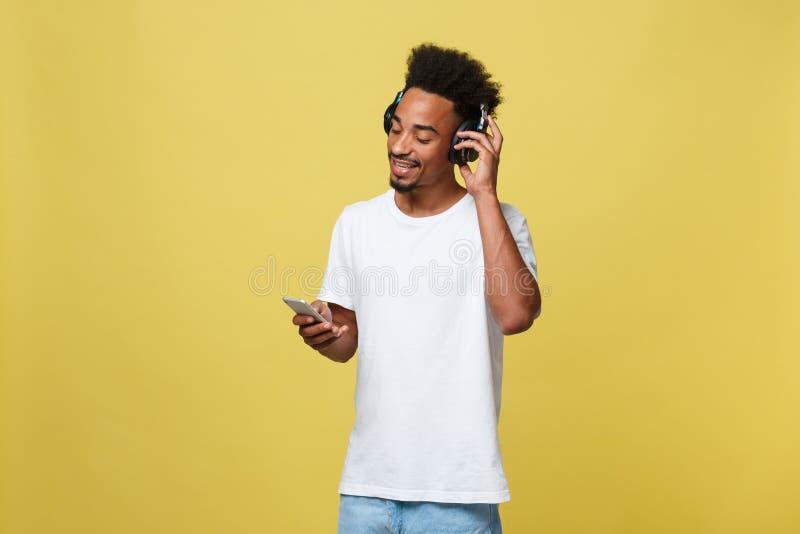 Modèle masculin africain beau de portrait avec la barbe écoutant la musique D'isolement au-dessus du fond jaune photographie stock libre de droits