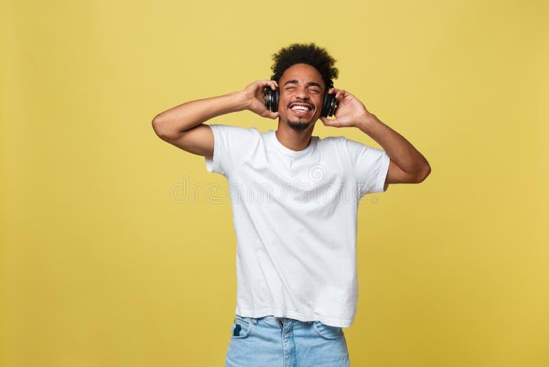 Modèle masculin africain beau de portrait avec la barbe écoutant la musique D'isolement au-dessus du fond jaune image stock
