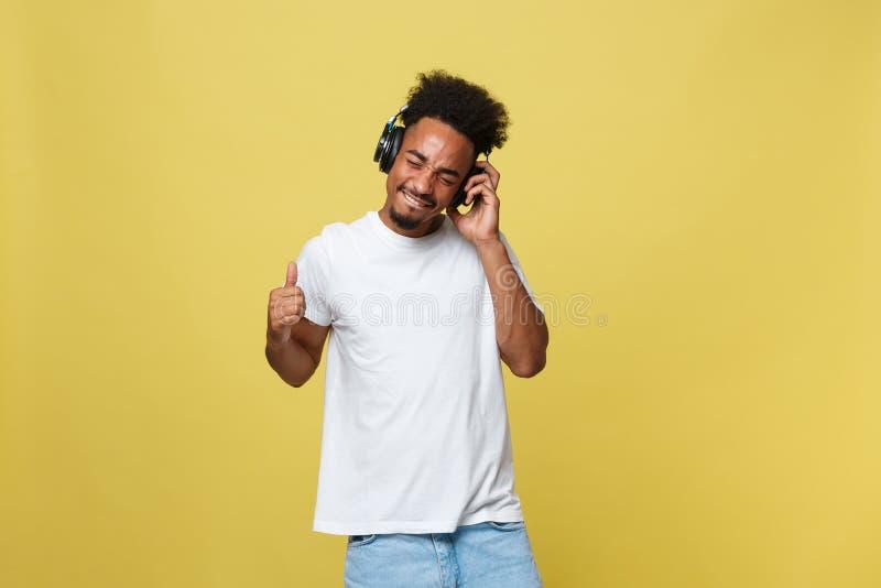 Modèle masculin africain beau de portrait avec la barbe écoutant la musique D'isolement au-dessus du fond jaune images stock