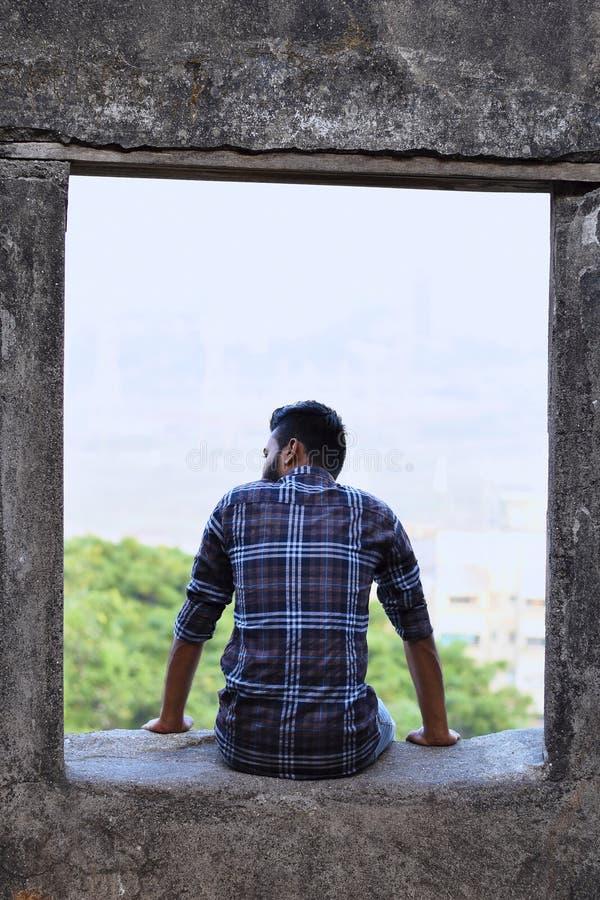 Modèle masculin avec le dos vers l'appareil-photo se reposant sur un rebord de roche photos stock