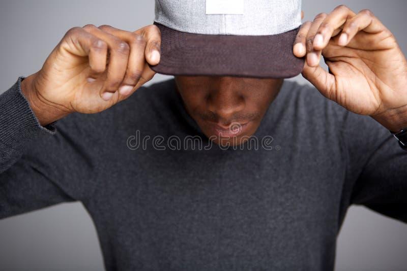 Modèle masculin d'afro-américain frais avec le chapeau regardant vers le bas photos libres de droits