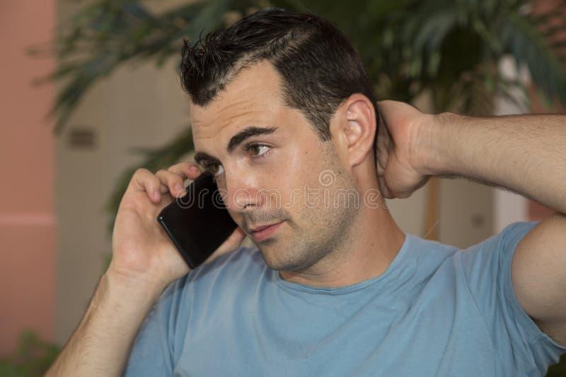 Modèle masculin d'une chevelure foncé dans la conversation de téléphone portable stressante image stock