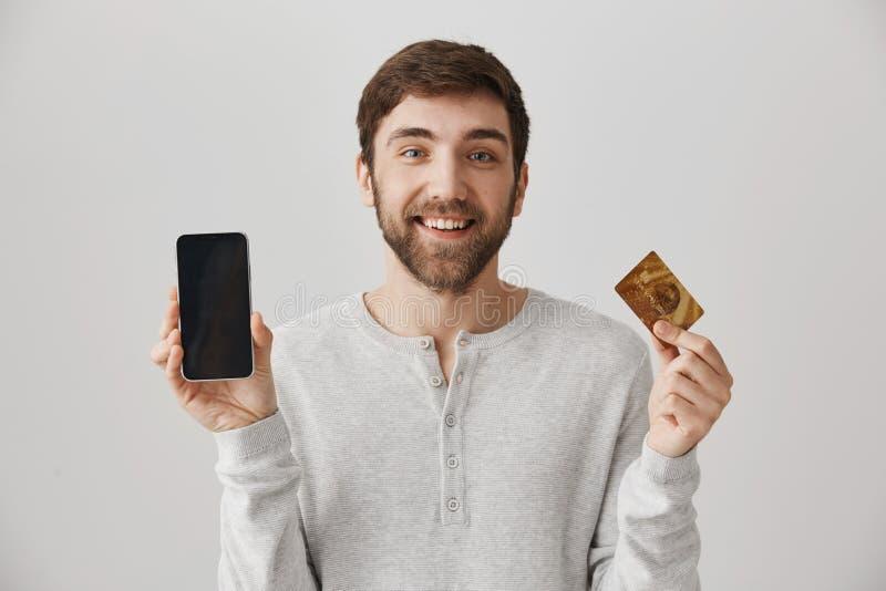Modèle masculin européen positif avec le sourire mignon montrant le smartphone et la carte de crédit à l'appareil-photo, se tenan photographie stock libre de droits