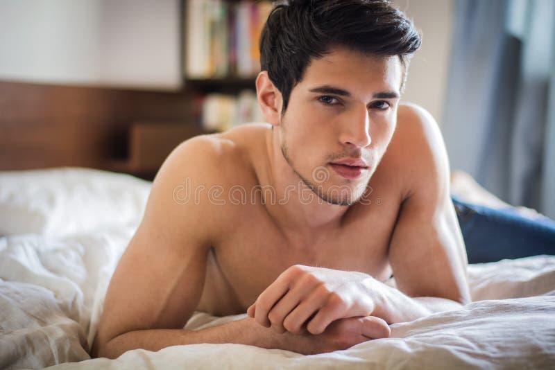 Modèle masculin sexy sans chemise seul se trouvant sur son lit images stock