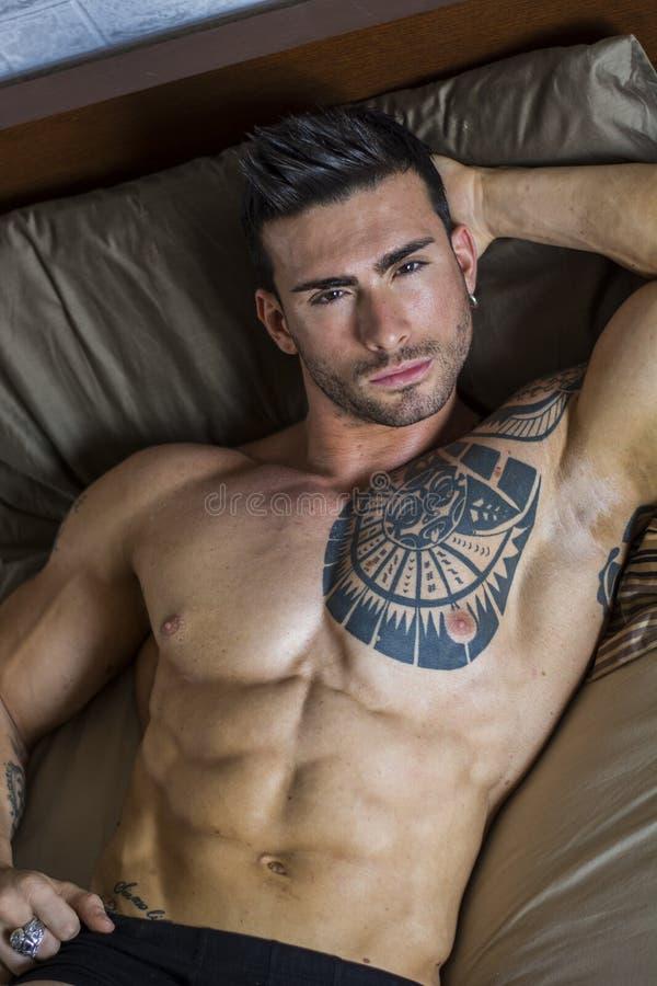 Modèle masculin sexy sans chemise seul se trouvant sur son lit photo libre de droits