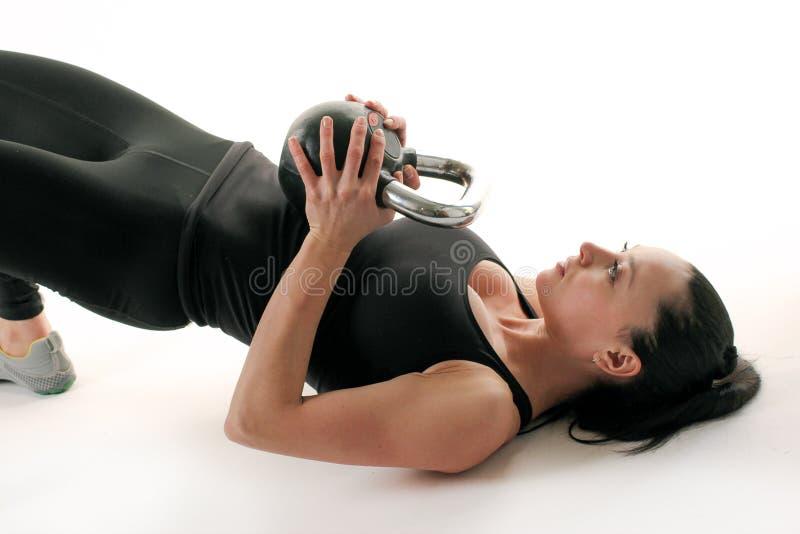Modèle mignon de forme physique tenant un kettlebell sur son coffre photographie stock