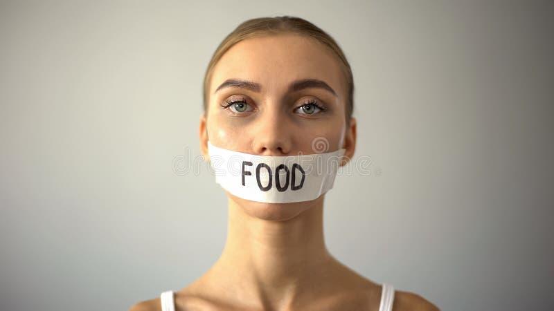 Modèle mince avec la bouche attachée du ruban adhésif, concept de la restriction de nourriture et anorexie, régime image stock
