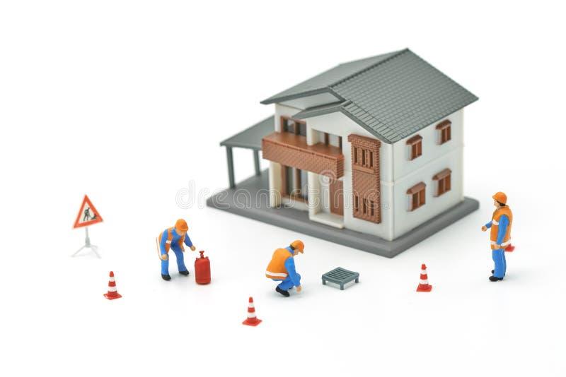 Modèle miniature de maison de modèle de la réparation A de travailleur de la construction de personnes utilisant en tant que le c image stock