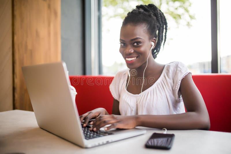 Modèle noir femelle gai se reposant dans la musique préférée de écoute de café dans des écouteurs et causant dans les réseaux Bel photos stock
