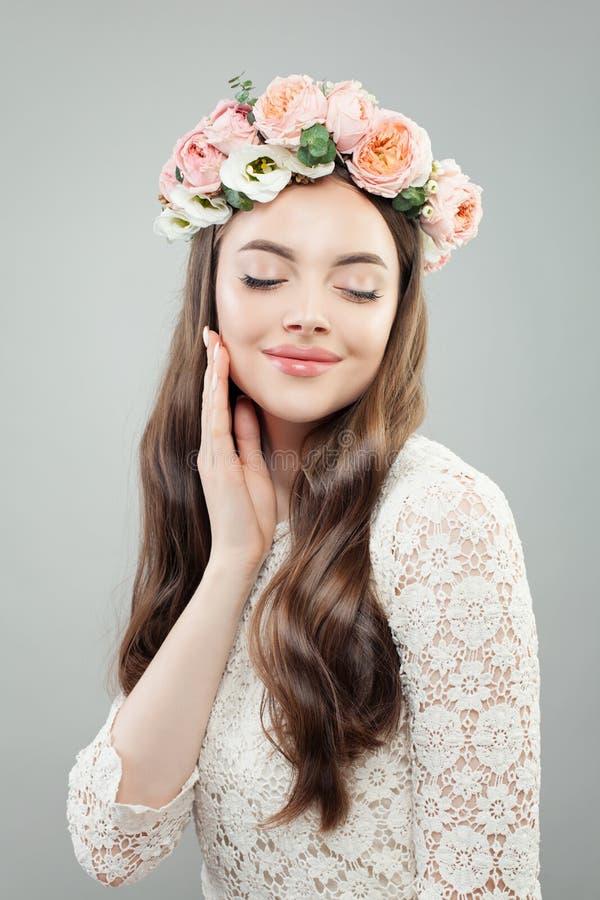 Modèle parfait de femme avec les cheveux bouclés, le maquillage et les fleurs La fille de détente, yeux s'est fermée photographie stock
