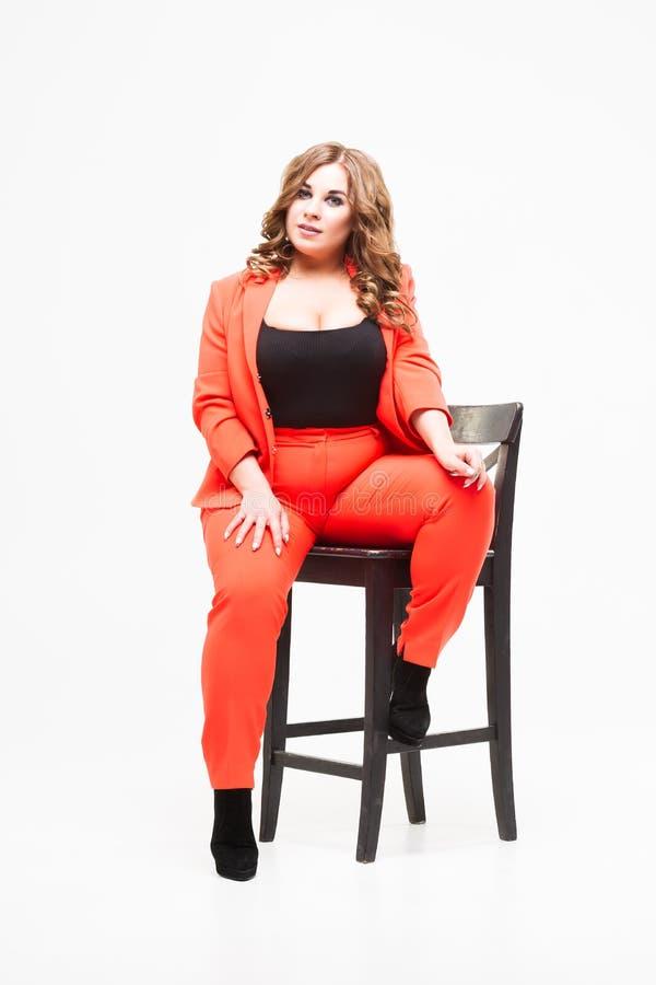 Modèle plus de taille avec le grand sein et la femme decollete et grosse profonde sur le fond blanc dans le pantsuit orange, conc images stock