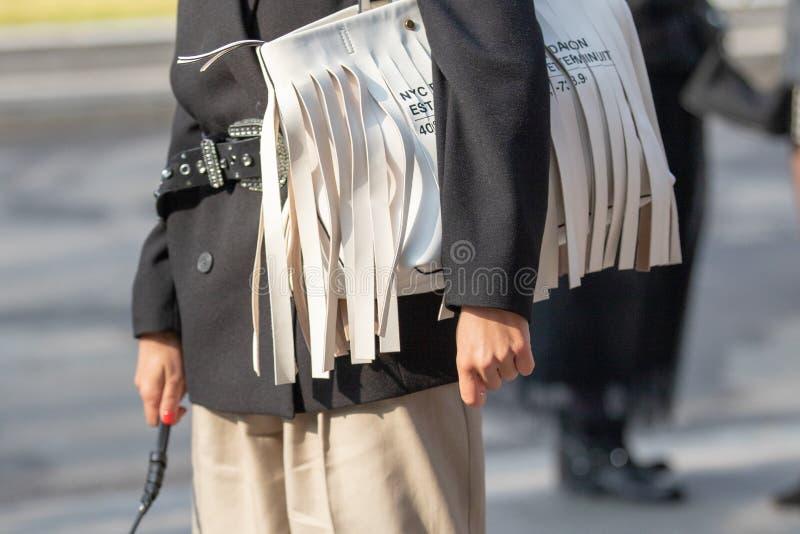 Modèle portant un sac d'épaule blanc avec des franges images libres de droits