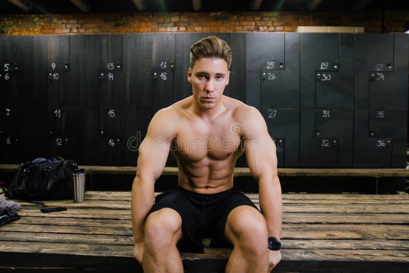 Modèle sérieux de forme physique d'un entraîneur masculin de bodybuilder s'asseyant sur un banc dans le vestiaire photographie stock