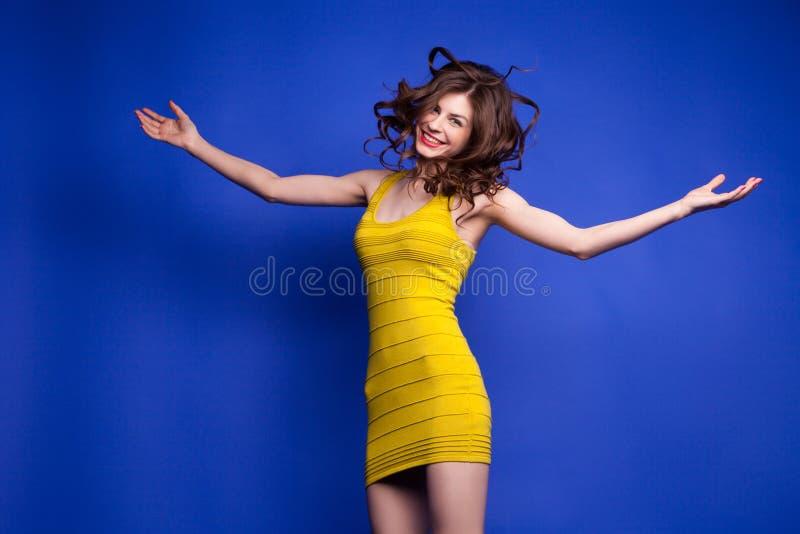 Modèle sautant heureux dans la robe jaune avec les bras tendus photos libres de droits