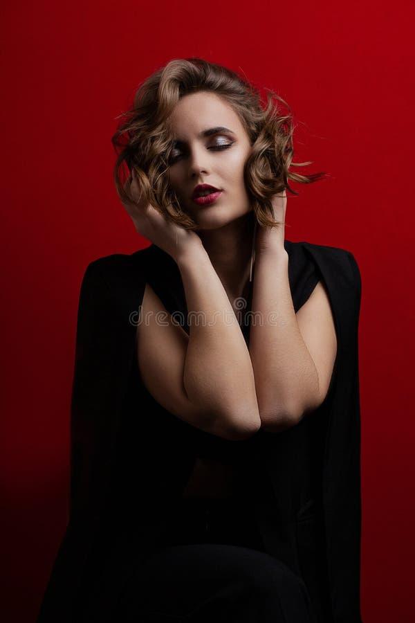 Modèle sensuel de brune avec les cheveux courts onduleux posant avec la lumière de contraste au fond rouge photographie stock libre de droits