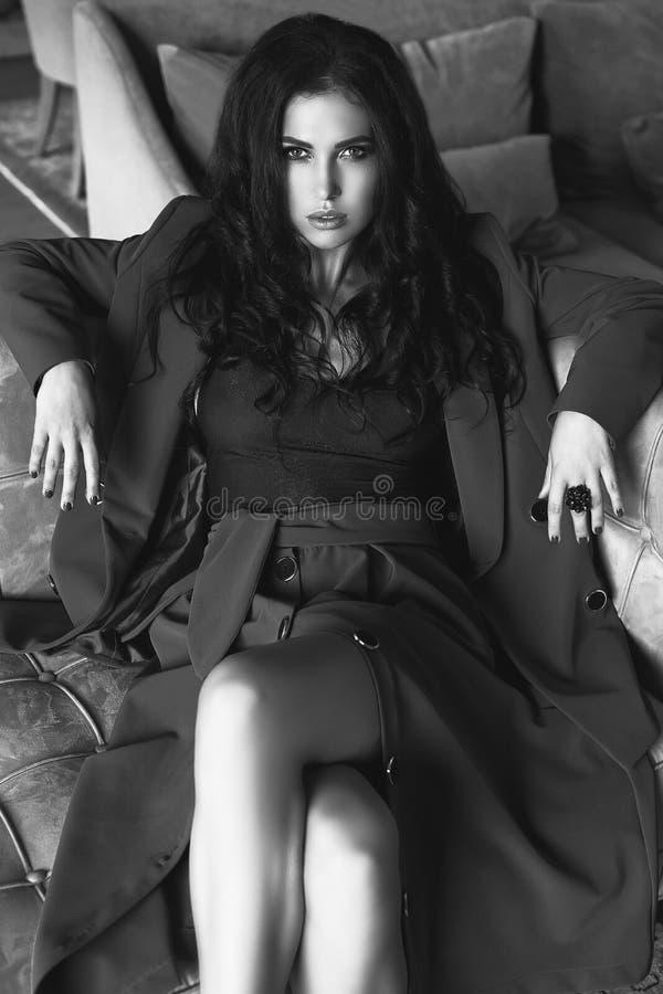 Modèle sensuel magnifique de brune dans le costume de mode détendant sur le couc photographie stock libre de droits