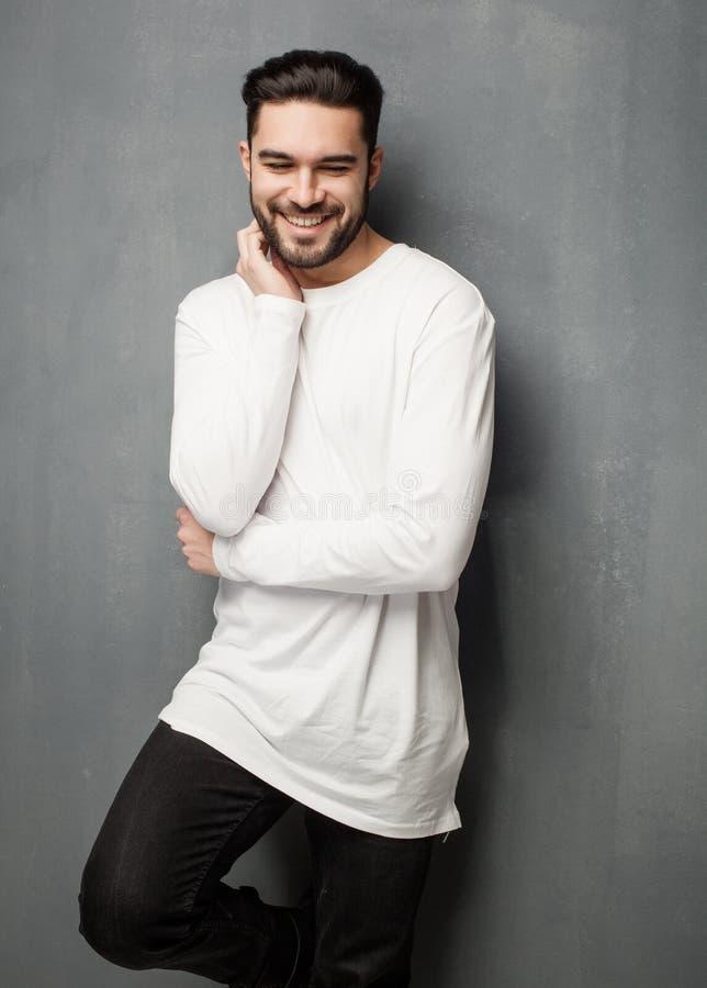 Modèle sexy d'homme de mode dans le chandail, les jeans et le sourire blancs de bottes photo stock