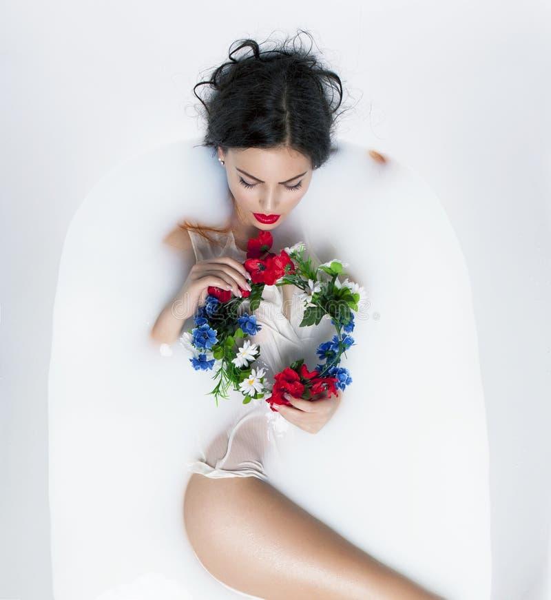 Modèle sexy de brune dans le bain de lait avec la couronne des fleurs photos stock