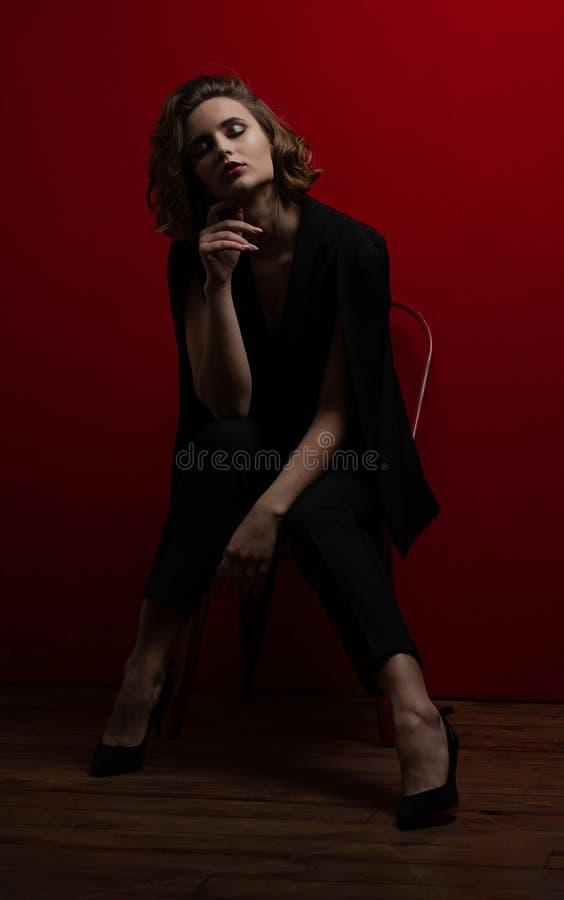 Modèle stupéfiant de brune avec les cheveux courts onduleux posant avec la lumière de contraste au fond rouge photos libres de droits